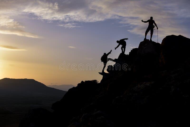 奋斗在倾斜的成功的小组登山人 免版税库存照片