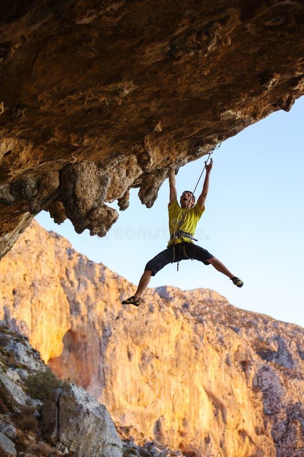 奋斗在峭壁的富挑战性路线的攀岩运动员 免版税库存照片