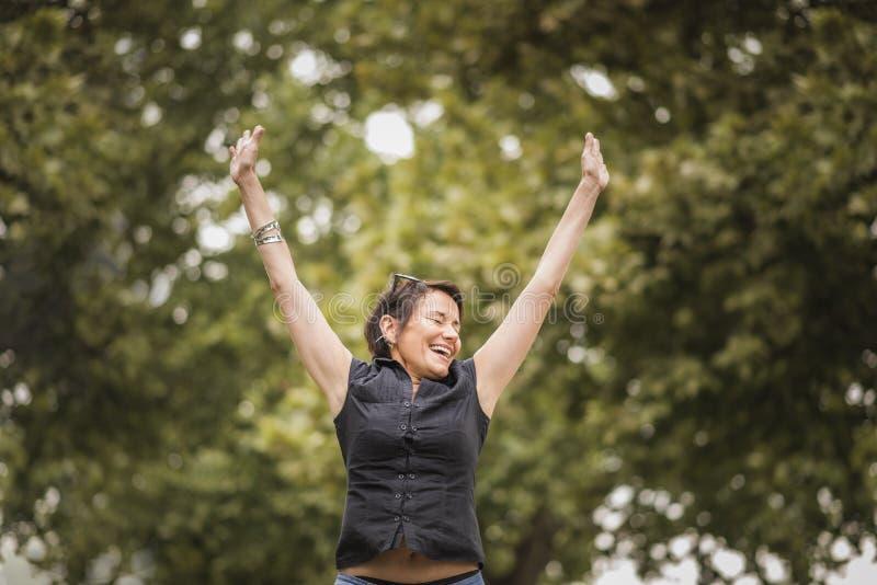 兴奋的和快乐成熟女实业家跳跃 免版税库存图片
