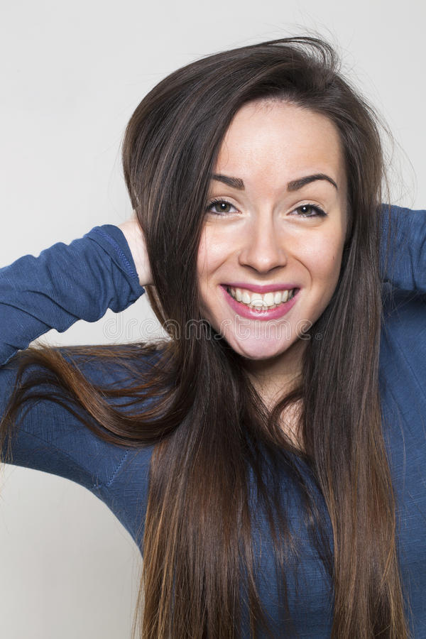 兴奋的少妇微笑的使用与健康的长的头发 图库摄影