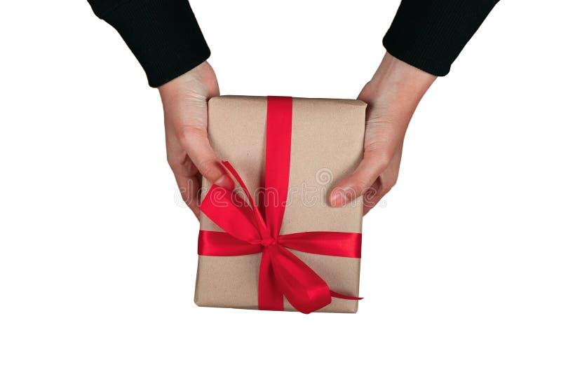 奖金人的人手给一个当前布朗礼物盒蝶形领结在白色背景隔绝的红色丝带有裁减路线顶视图 库存照片
