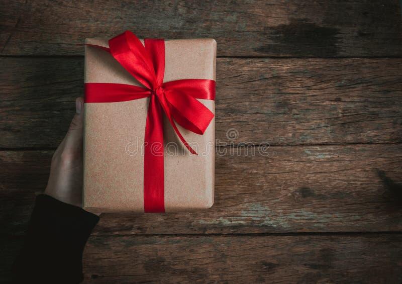 奖金人的人手给一个当前布朗礼物盒蝶形领结在老木地板顶视图圣诞快乐和愉快新的红色丝带 库存图片