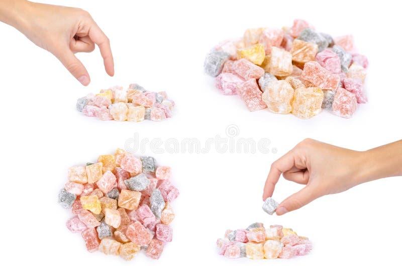 套不同的土耳其快乐糖甜点用手,隔绝在白色背景,上色了糖果,自然产品 免版税库存照片