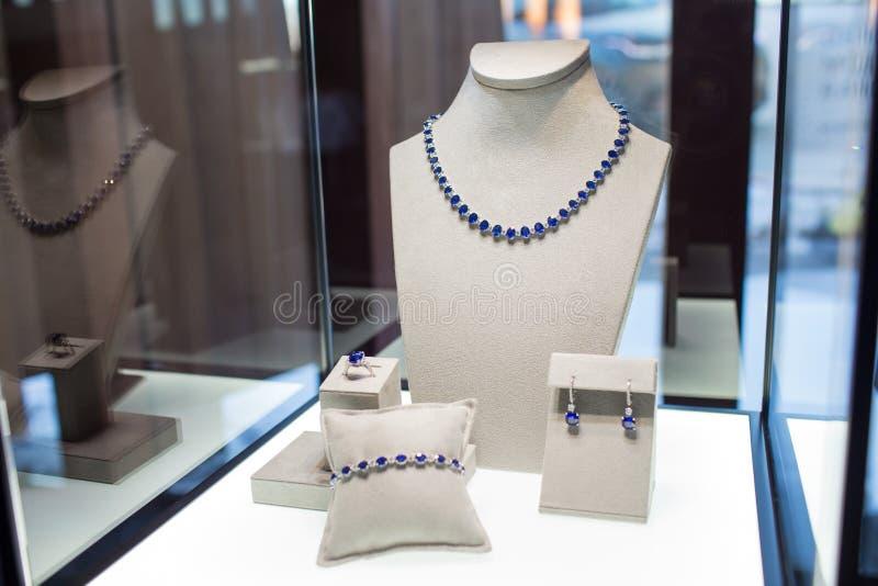 套与蓝宝石的首饰:项链、镯子、圆环和耳环 免版税库存照片