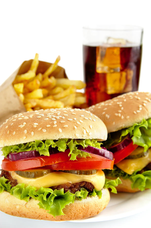 套两个乳酪汉堡,炸薯条,杯在板材的可乐 库存图片