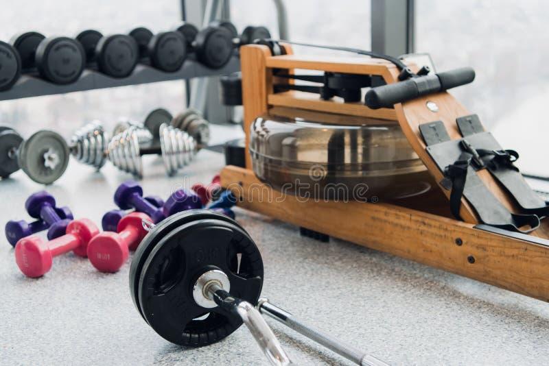 套举重和健身的设备:哑铃、杠铃和划船器在健身房 库存照片