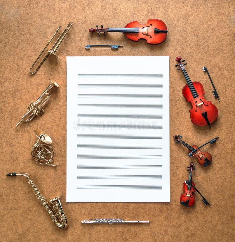 套五金黄铜管乐器和四串起乐队乐器和放在他们之间的活页乐谱 免版税库存图片