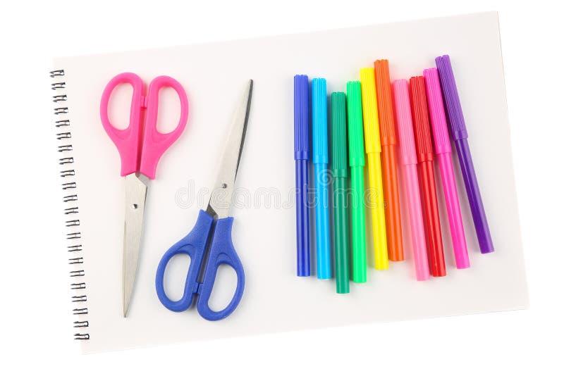 套五颜六色的毡尖笔和两把剪刀在空白,被打开的写生簿板料,隔绝在白色背景 艺术和creativi 图库摄影