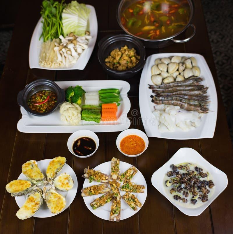 套亚洲海鲜用椰子Escargot,烤肉竹蛏,乳酪烤牡蛎,煮沸了吃与结辨的鱼的菜 免版税库存照片