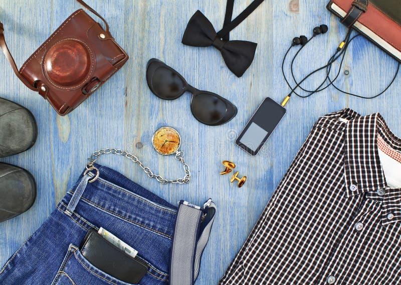 套人的衣物和辅助部件在蓝色木桌上 库存照片