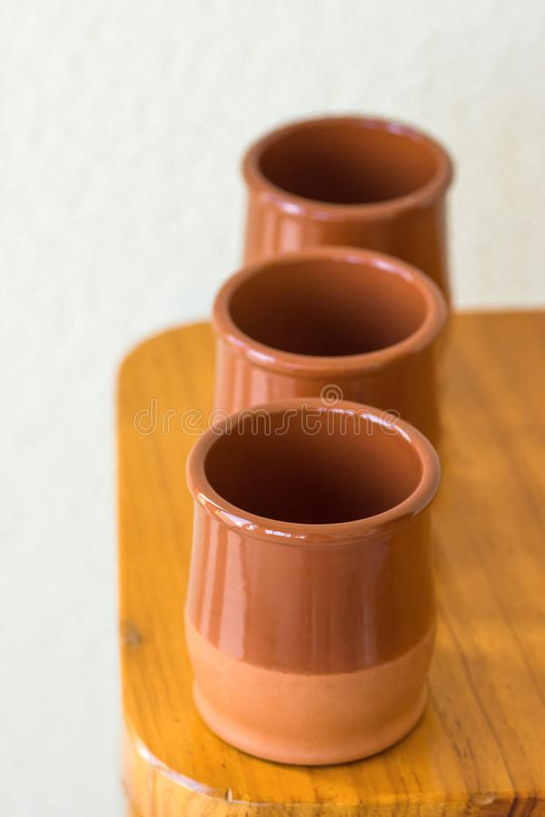 套传统西班牙红土给在木桌上的陶器杯子上釉 地中海厨房内部 地方传统手工的工艺 免版税图库摄影