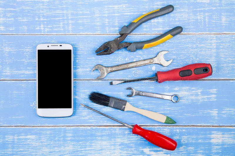 套修理在白色木背景的手工具与smartph 免版税库存照片