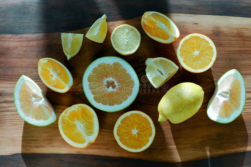 套切的柑橘水果柠檬,石灰,桔子,在木背景的葡萄柚 顶视图 免版税库存照片