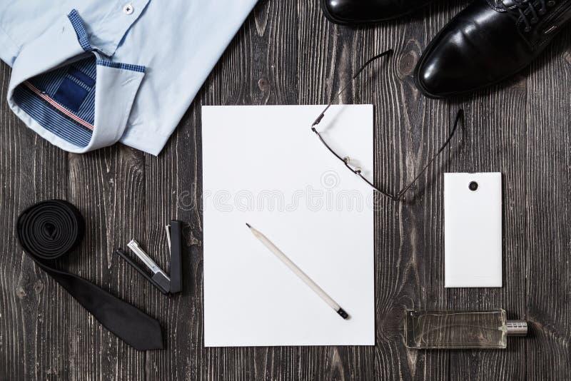 套商人时装配件和白纸在中间,顶视图在白色木背景 免版税库存照片