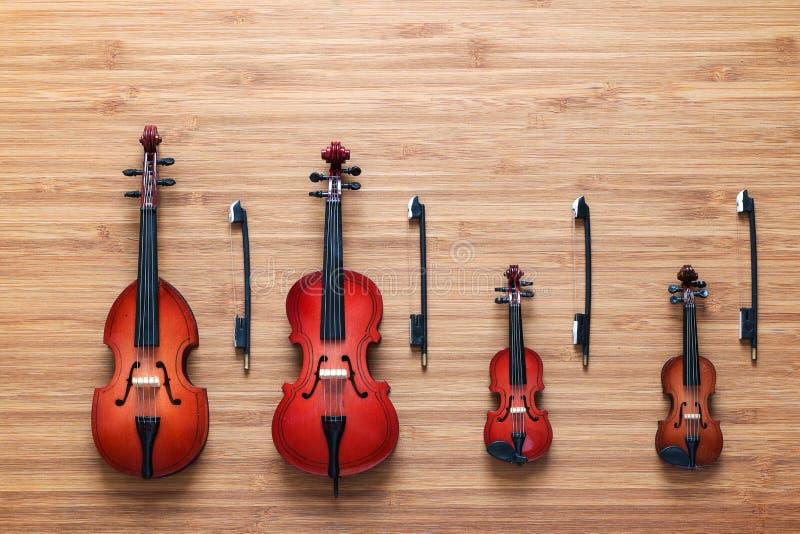 套四个玩具串乐队乐器:小提琴,大提琴,低音提琴,在木背景的中提琴 概念电吉他例证音乐 免版税库存图片