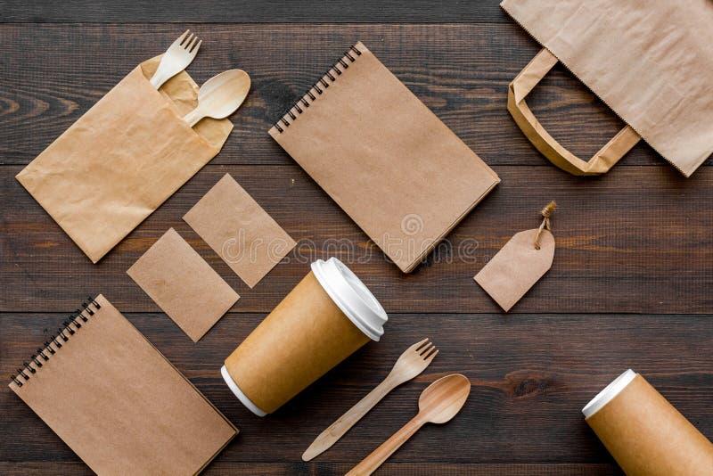 套回收包装纸袋子,一次性碗筷杯子,匙子,叉子,在木背景顶视图样式的笔记本 库存照片