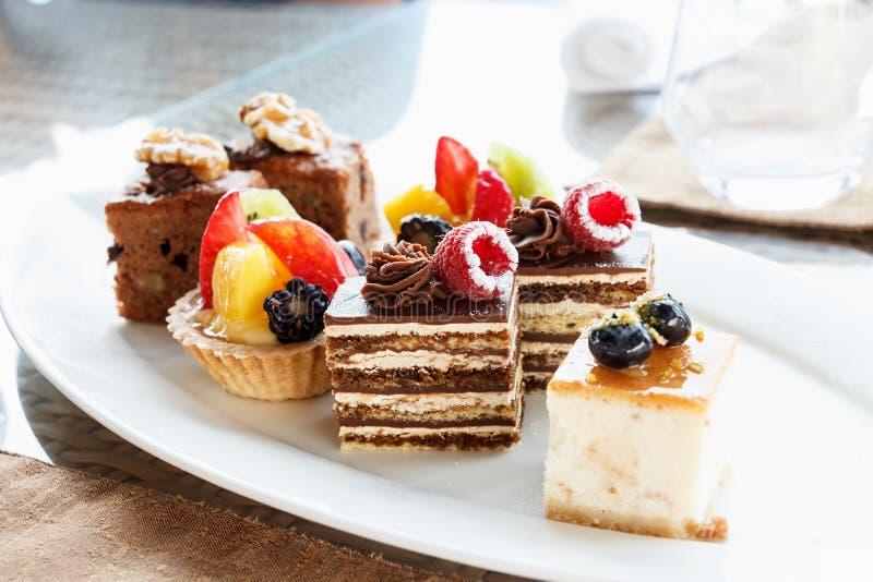 套在分类的微型蛋糕在白色板材 婚姻正餐肉卷熏制的蕃茄 巧克力蛋糕用莓 果子馅饼用果子 免版税库存照片