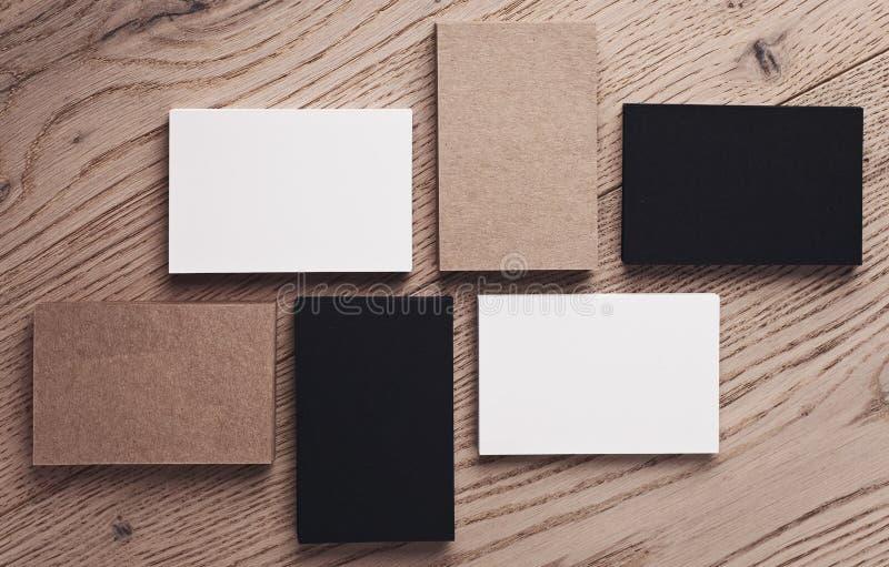 套在木桌上的白色,黑和工艺名片 顶视图 水平 免版税库存照片