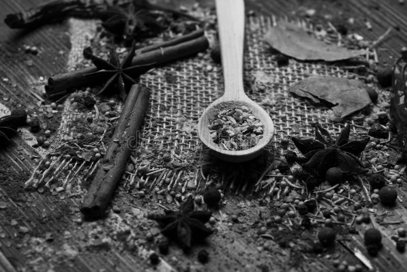 套在木背景,关闭的香料 木匙子用干燥香料、肉桂条和茴香星 库存图片