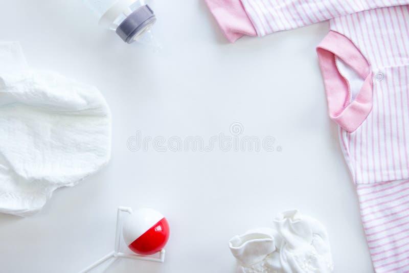套在桌上的婴孩供应:尿布,装豆子小布袋,瓶,衣服 免版税库存图片