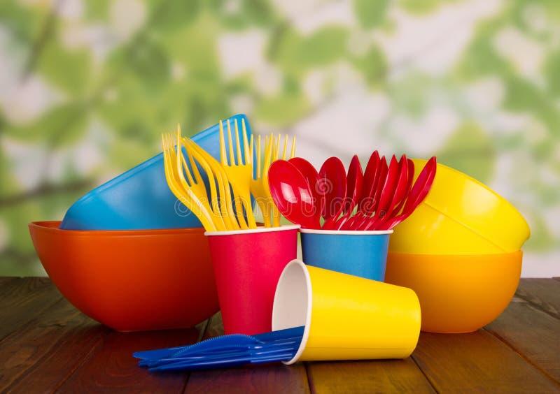 套在浅绿色的背景的一次性塑料碗筷 免版税库存照片