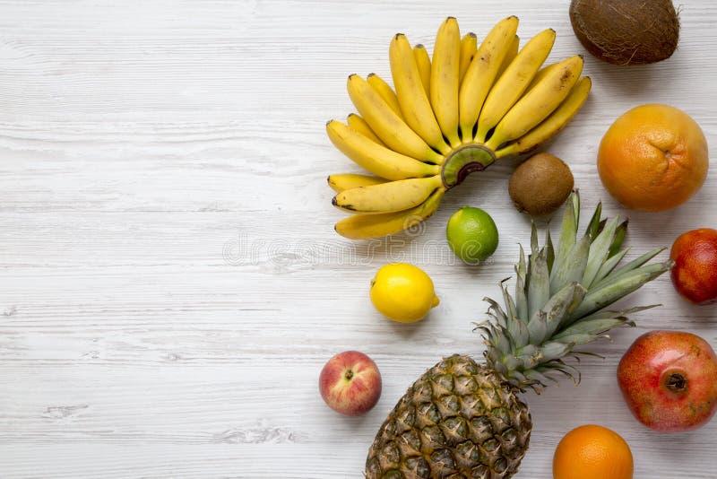 套在白色木背景的新鲜的热带水果,从上面 复制空间 图库摄影