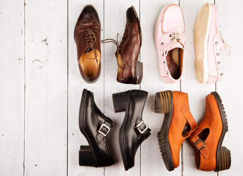 套在白色木背景的男女皆宜的鞋子 库存图片