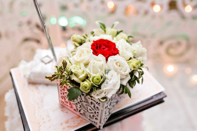套在红色和白色玫瑰的婚戒被采取的特写镜头 新娘概念礼服婚姻纵向的台阶 选择聚焦 花的布置箱子为 库存图片
