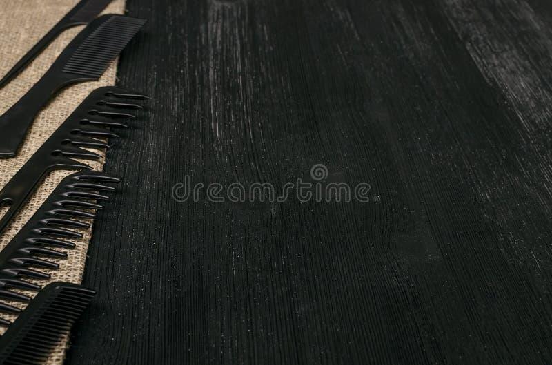 套在麻袋布粗麻布背景的另外黑发梳子 免版税库存照片