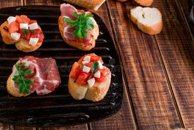 套在黑格栅平底锅木背景的bruschetta 鲜美开胃小菜 图库摄影