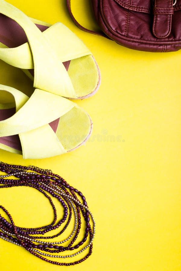 套妇女的对夏季的事辅助部件 布朗袋子黄色平台凉鞋,项链 平的位置 库存照片