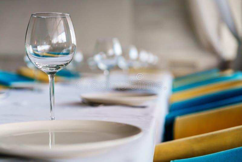 套干净的空的酒杯和板材在餐桌上与五颜六色的椅子在餐馆内部淡色背景 关闭 免版税库存照片