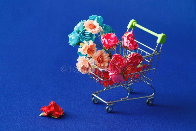 套手工制造的多彩多姿的纸花和在从超级市场的一个篮子设计,一朵花在ba的轮子附近落 库存照片