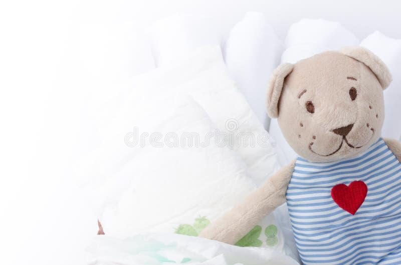 套新出生的尿布在与爱熊玩具的篮子 婴孩分类 免版税图库摄影