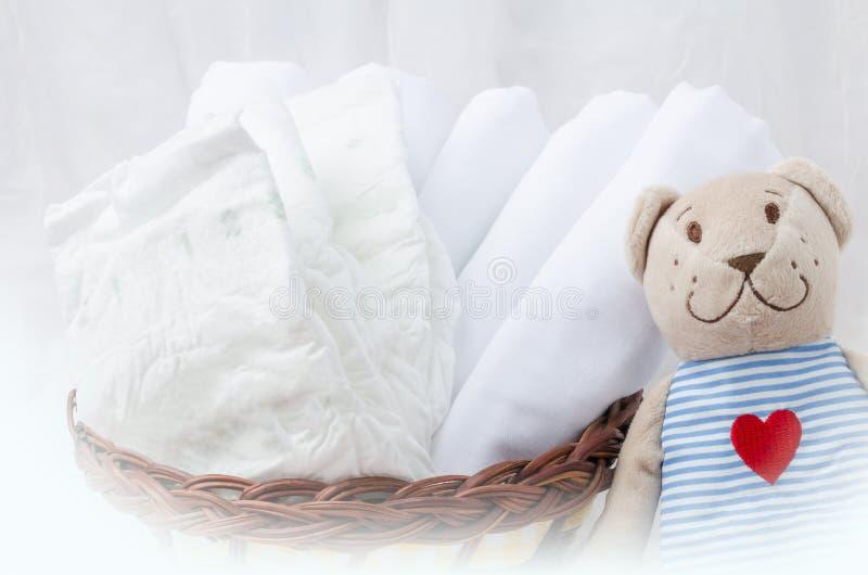 套新出生的尿布在与爱熊玩具的篮子 婴孩分类 库存照片