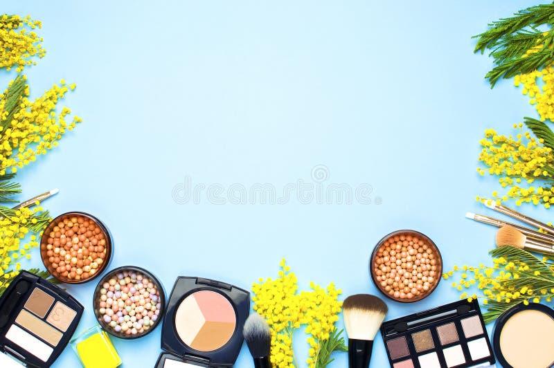 套构成粉末胭脂眼影膏纠正者刷子的装饰含羞草化妆用品和花在蓝色背景的 构成 免版税库存照片