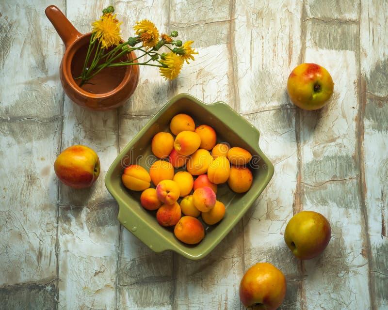 套果子油桃和杏子在一块绿色方形的板材在一张轻的桌上,射击从油罐顶部角钢,一个小花瓶与 免版税库存图片