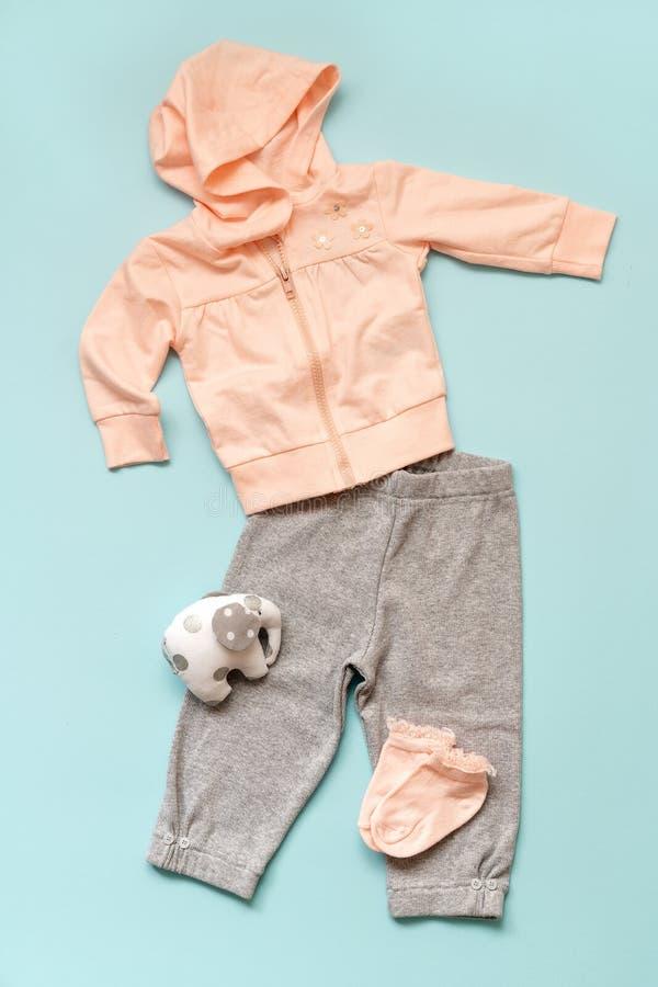 套桃红色儿童` s在蓝色背景穿衣 扭转与敞篷、灰色裤子、袜子和大象` s玩具 免版税库存照片