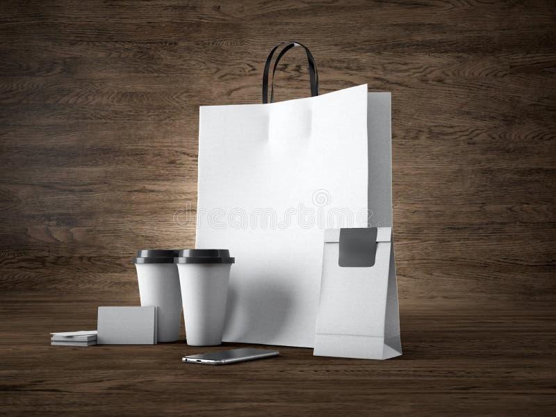 套白色购物袋,拿走杯子、纸包裹、空白的名片和普通设计智能手机 木头 图库摄影
