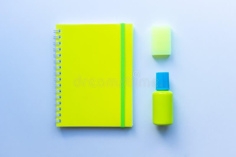 套的顶视图文具:与绿色条纹的黄色笔记薄,黄色橡皮擦和蓝色和黄色掩没的流体在白色后面 免版税图库摄影