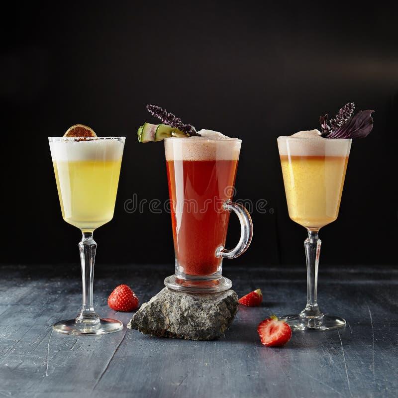 套红色和黄色酒精鸡尾酒在黑暗的Backgro关闭  免版税图库摄影