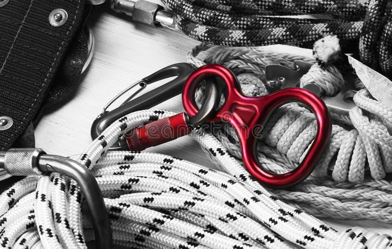 套绳索和carabiners攀岩的 在黑白的颜色 下降的红色设备 免版税库存图片