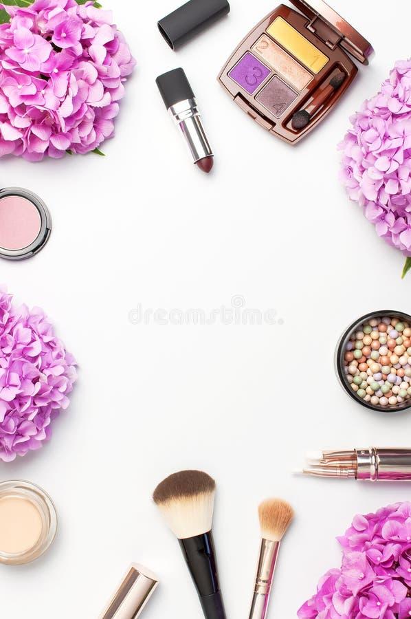 套装饰化妆用品染睫毛油粉末唇膏眼影膏脸红构成刷子桃红色在轻的背景上面的八仙花属花 免版税库存照片