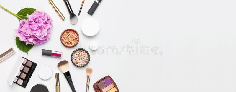 套装饰化妆用品染睫毛油粉末唇膏眼影膏脸红构成刷子桃红色在轻的背景上面的八仙花属花 库存图片
