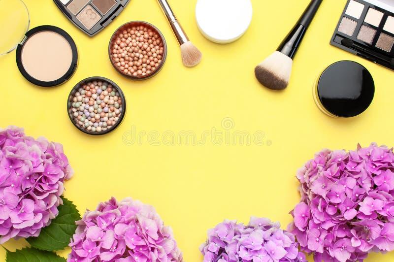 套装饰化妆用品染睫毛油粉末唇膏眼影膏脸红构成刷子桃红色在黄色背景上面的八仙花属花 免版税库存图片
