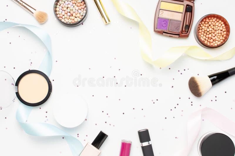 套装饰化妆用品染睫毛油粉末唇膏眼影膏脸红构成刷子,星五彩纸屑在光的假日丝带 图库摄影