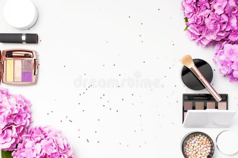 套装饰化妆用品染睫毛油粉末唇膏眼影膏脸红花担任主角在光的五彩纸屑的构成刷子桃红色八仙花属 库存照片
