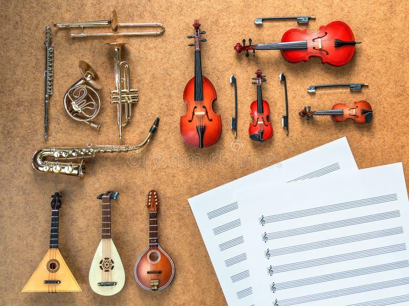 套金黄铜管乐器乐队仪器:萨克斯管、喇叭、说谎在它附近的法国号、伸缩喇叭和被弄皱的活页乐谱 免版税库存图片