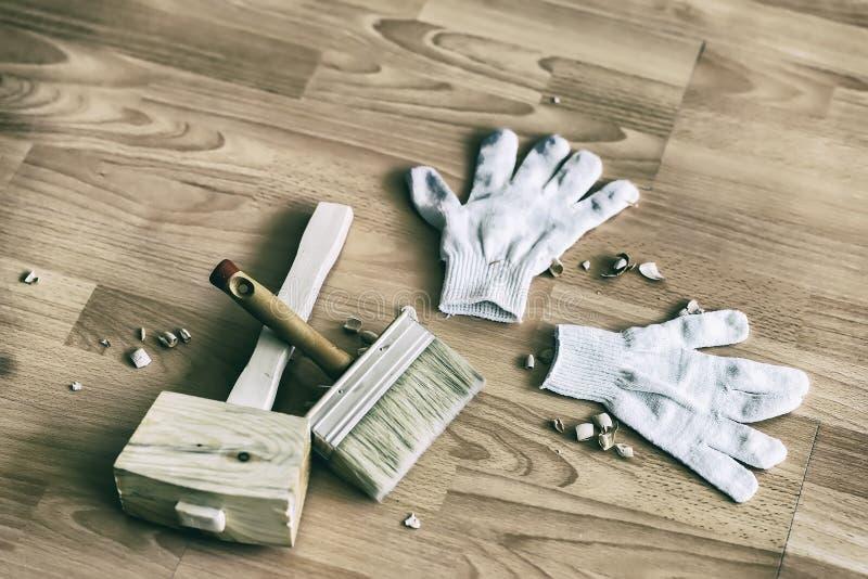 套锤子,手套,在地板,被定调子的图象上掠过左  手工制造,职业化和爱好的概念 免版税库存照片