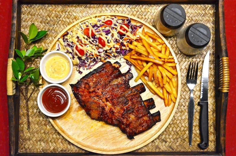 套BBQ肋骨烤了与法语油煎的和沙拉的牛排在竹盘子背景 免版税库存照片